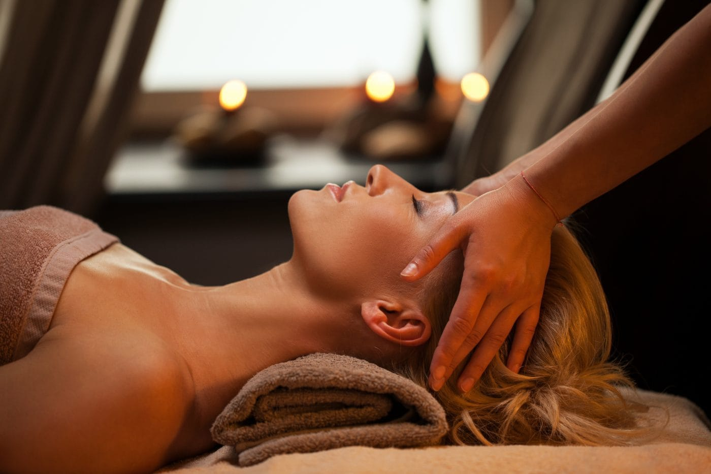 Beautiful young woman enjoys massage in a luxury spa resort